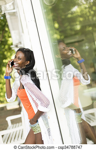 Young african woman with mobile phone - csp34788747