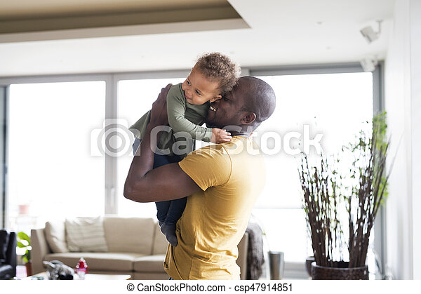 Young afro-american father with his little daughter at home. - csp47914851