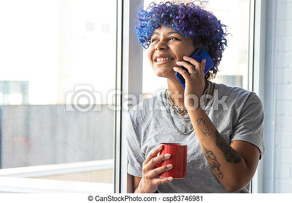 young afro american woman with mobile phone and cup of coffee at the window - csp83746981