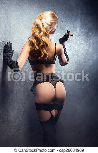 b667b45abd0 Young and beautiful cabaret dancer in sexy vintage lingerie smoking ...