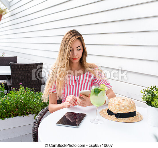 Young and beautiful girl in cafe with long hair. Reads a message on phone, online on Internet for lunch in restaurant. In summer on sun porch. On the table is a glass of green lime and a tablet. - csp65710607