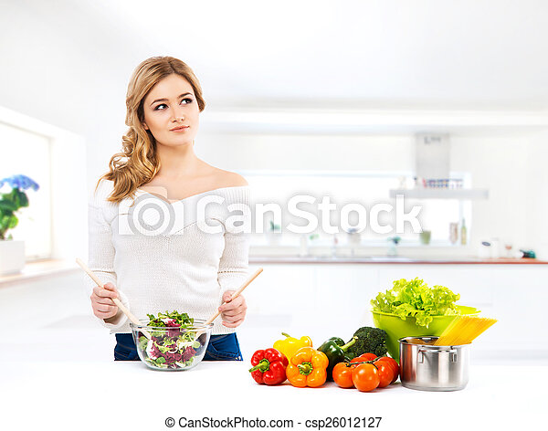 Young and beautiful housewife woman cooking in a kitchen - csp26012127