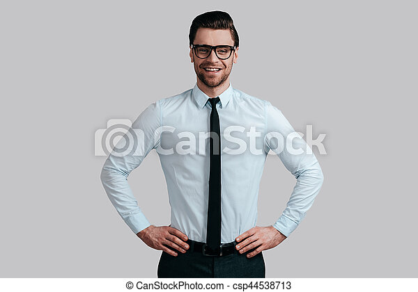 9ee8cb02005 Young And Successful. Good Looking Young Man In Eyeglasses Keeping Hands On  Hip And Looking At