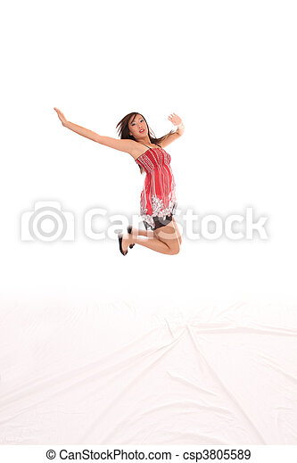 Young Asian American teen woman jumping red dress - csp3805589