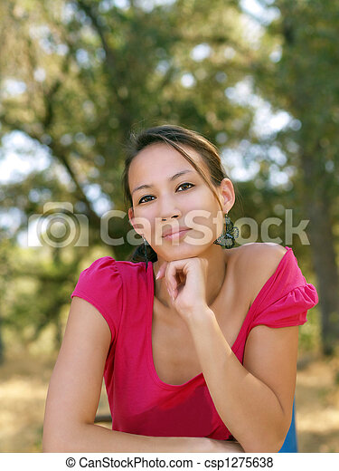 Young asian american woman portrait outdoors pink top - csp1275638