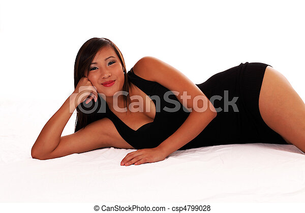 Young Asian American woman reclining in black dress - csp4799028
