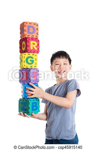 Young asian boy holding alphabet blocks over white background - csp45915140