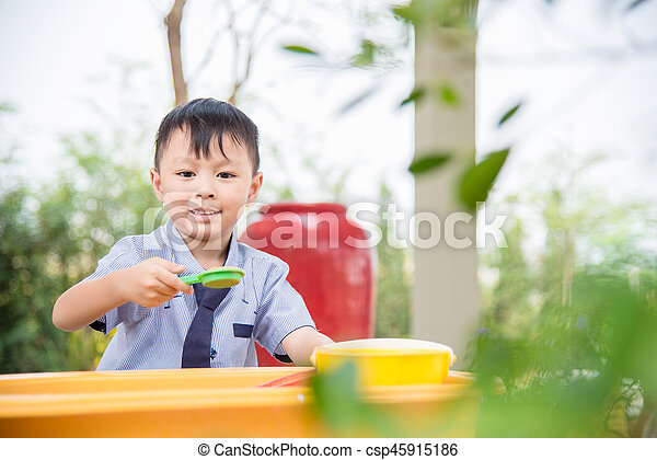 Young asian boy playing sand in sandbox - csp45915186