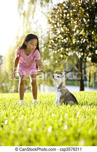 Young Asian girl training puppy to sit - csp3576311