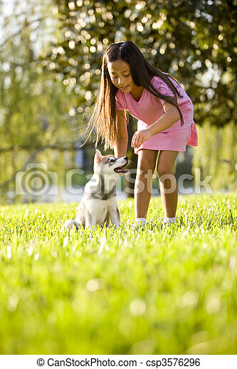 Young Asian girl training puppy to sit - csp3576296