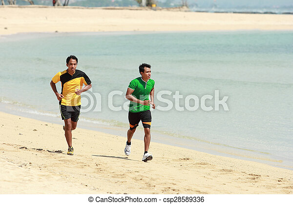 Young Asian man running on beach, Sport concept - csp28589336