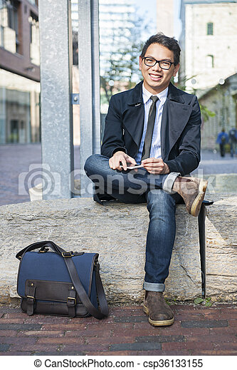 Young asian man sitting outside - csp36133155