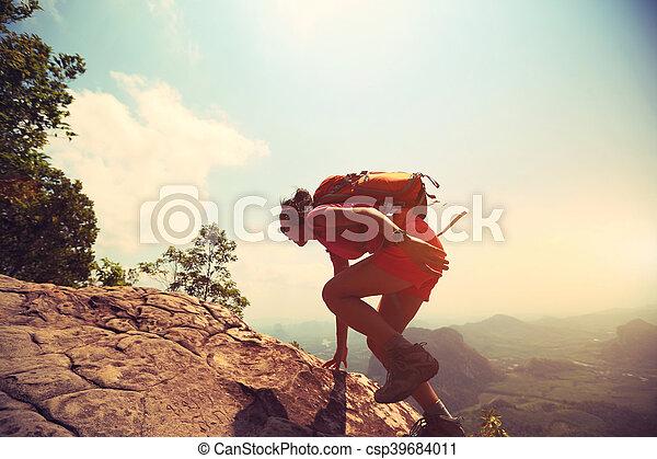 young asian woman hiker climbing rock on mountain peak cliff - csp39684011