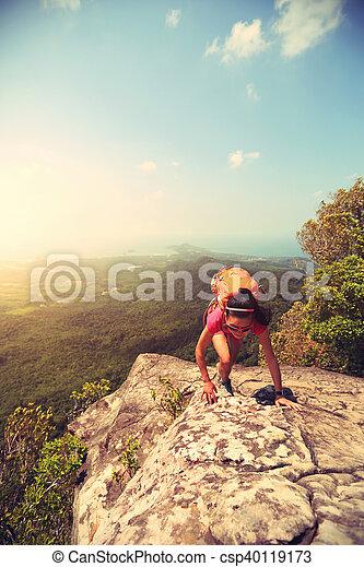 young asian woman hiker climbing rock on mountain peak cliff - csp40119173