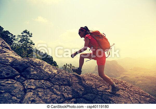 young asian woman hiker climbing rock on mountain peak cliff - csp40119180
