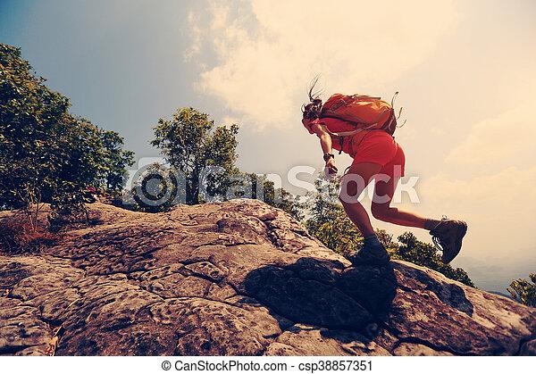 young asian woman hiker climbing rock on mountain peak cliff - csp38857351