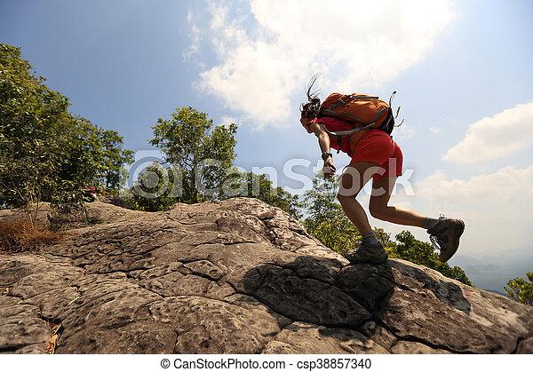 young asian woman hiker climbing rock on mountain peak cliff - csp38857340