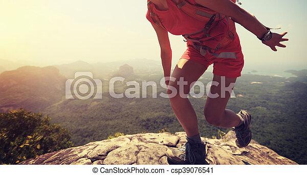 young asian woman hiker climbing rock on mountain peak cliff - csp39076541
