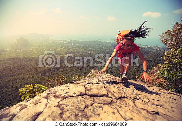 young asian woman hiker climbing rock on mountain peak cliff - csp39684009