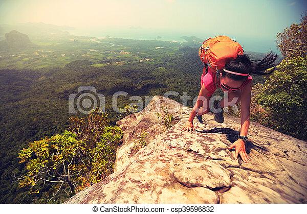 young asian woman hiker climbing rock on mountain peak cliff - csp39596832