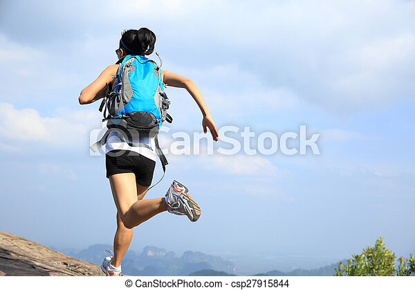 young asian woman hiker running on mountain peak cliff - csp27915844
