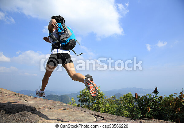 young asian woman hiker running on mountain peak cliff - csp33566220
