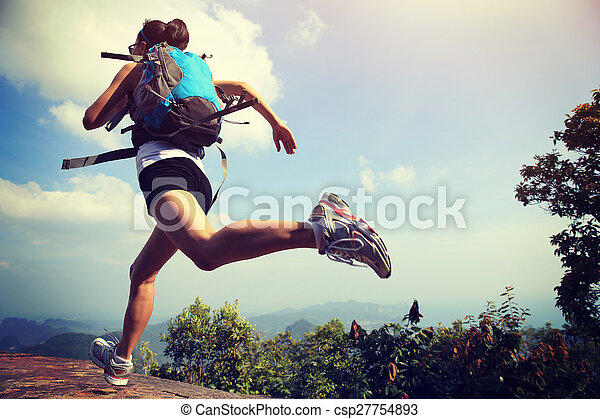 young asian woman hiker running on mountain peak cliff - csp27754893