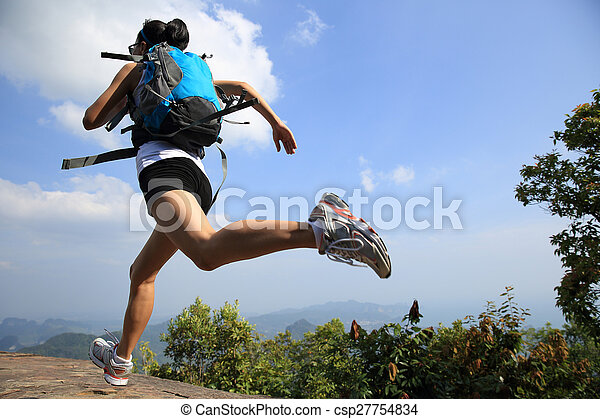 young asian woman hiker running on mountain peak cliff - csp27754834