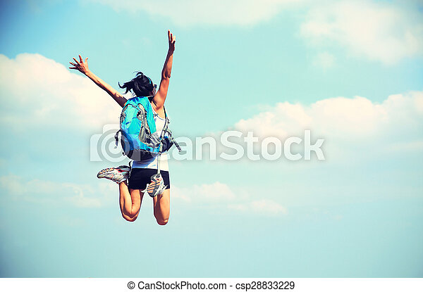 young asian woman jumping against blue sky - csp28833229