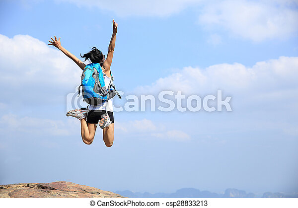 young asian woman jumping on mountain peak cliff - csp28833213