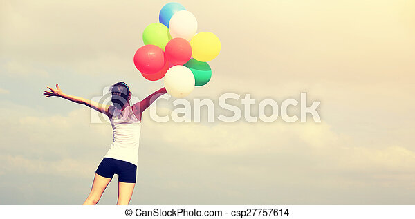 young asian woman on mountain peak rock with colored balloons - csp27757614