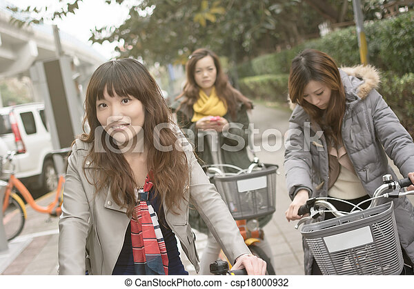 Young Asian woman riding bicycle with friends - csp18000932
