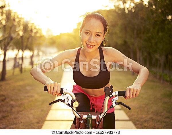 young asian woman riding bike outdoors at sunset - csp27983778