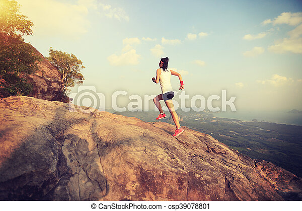young asian woman runner running on mountain peak - csp39078801