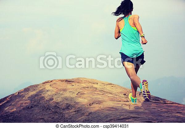 young asian woman runner running on mountain peak - csp39414031