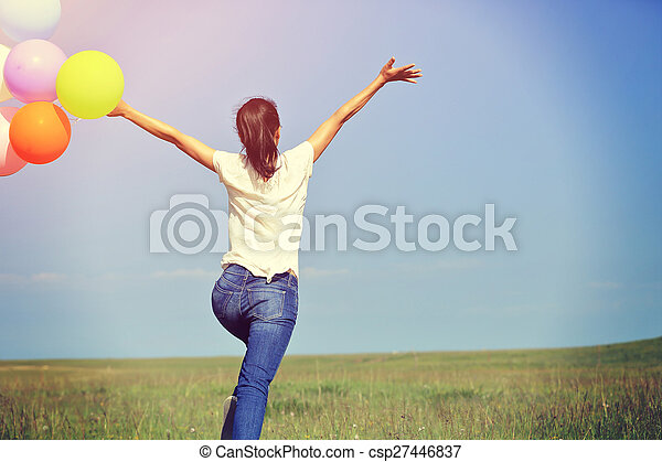 young asian woman running and jumping on green grassland with colored balloons - csp27446837