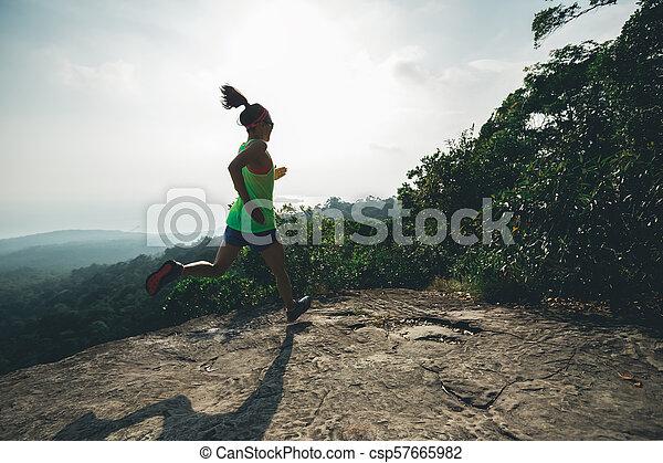 Young asian woman running on mountain peak - csp57665982