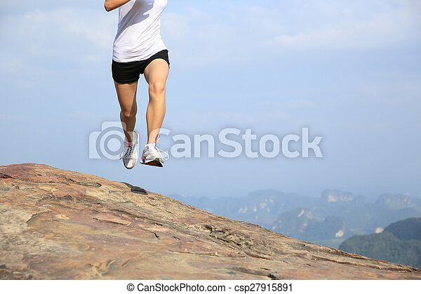 young asian woman running on mountain peak cliff - csp27915891