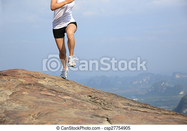 young asian woman running on mountain peak cliff - csp27754905