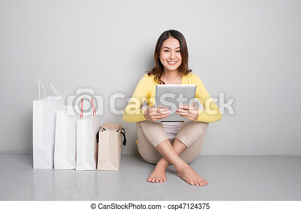 Young asian woman shopping online at home sitting besides row of shopping bags - csp47124375
