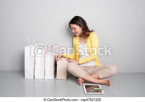 Young asian woman shopping online at home sitting besides row of shopping bags - csp47631220
