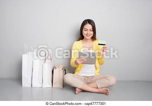 Young asian woman shopping online at home sitting besides row of shopping bags - csp47777301