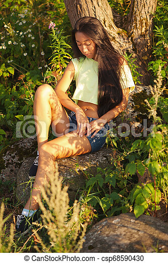 Young asian woman sitting on stone - csp68590430
