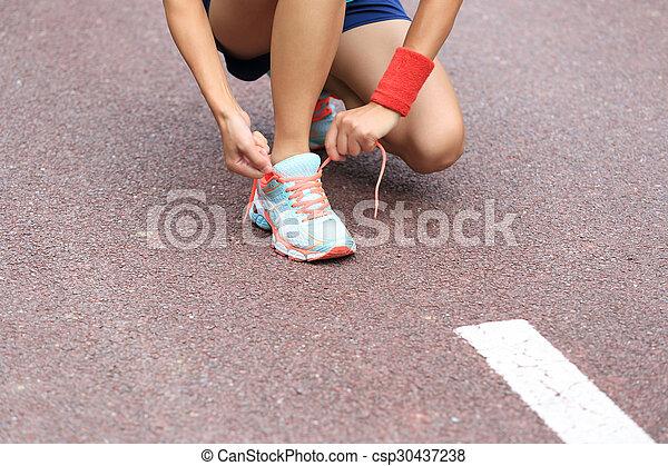young asian woman tying shoelace - csp30437238