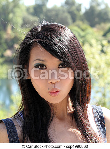 Young Asian woman with surpised expression outdoors - csp4990860