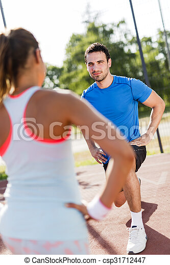 Young athletic man and woman stretching outdoors on a hot summer day - csp31712447
