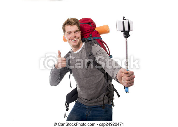 young atractive traveler backpacker taking selfie photo with stick carrying backpack ready for adventure - csp24920471