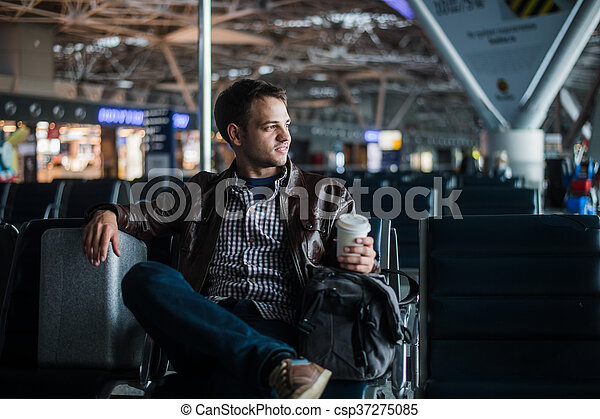 Young attractive man at the airport with his bag suitcase and coffee - csp37275085