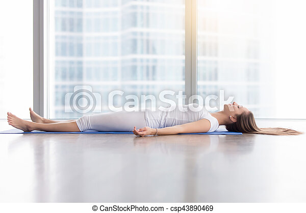 young attractive woman in corpse pose against floor window