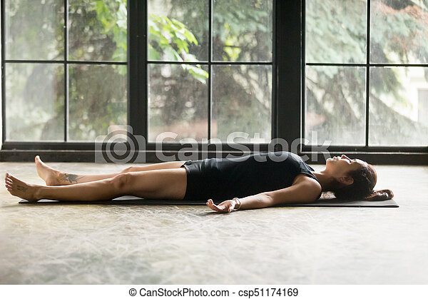 young attractive woman in corpse pose studio background